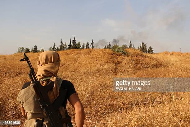 A rebel fighter looks at smoke billowing in the background during clashes with progovernment forces south of the northern Syrian city of Aleppo on...