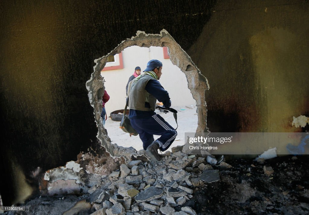 A rebel fighter moves through a hole punched in a wall near the front line fighting on Tripoli Street in downtown Misrata April 18, 2011 in Misrata, Libya. Tripoli Street once was Misrata's posh main avenue for shops and expensive apartments. Now weeks of house-to-house battles between forces loyal to Libyan ruler Moammar Gaddafi and rebels have left it in ruins. Fighting continues between Libyan government forces that have surrounded the city and anti-government rebels ensconced there, as the Libyan uprising enters its third month.