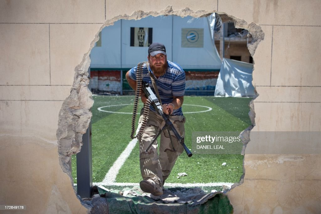 A rebel fighter passes through an access hole broken in the perimeter of a football pitch, close to the front line, where clashes between the rebels and pro-government troops have been taking place on the outskirts of the northern city of Aleppo, on July 4, 2013. Syria's President Bashar al-Assad accused the West of sending 'takfiri terrorist groups' to his country as a way to get rid of them, in an interview with a Syrian daily published.
