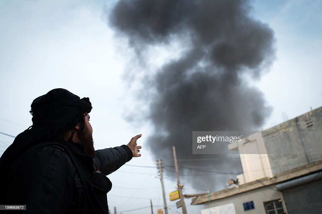 A Rebel fighter points at smoke rising in the city of Aleppo on January 18, 2013. UN leader Ban Ki-moon warned that Syria is in a 'death spiral', as his top humanitarian and human rights officials pleaded with the UN Security Council to take firmer action.