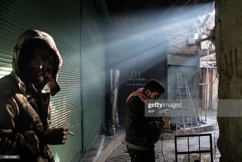 A rebel fighter (R) prepares the wires of a car-mounted camera used to spy on Syrian government forces while his comrade smokes a cigarette in the Bab al-Nasr district of Aleppo's Old City, on January 7, 2012. Syria's domestic opposition snubbed a call to dialogue from President Bashar al-Assad, as NATO powers challenged the leader's defiant grip on power and dispatched Patriot missile batteries to neighbouring Turkey.