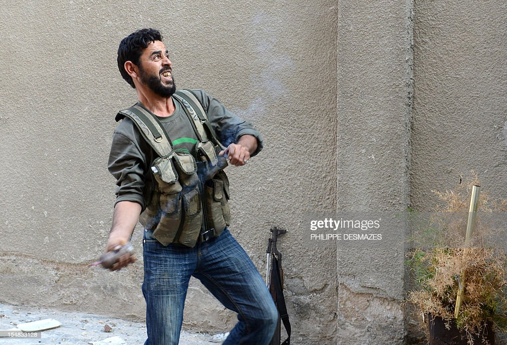 A rebel fighter readies to throw a handmade hand grenade towards pro-Syrian government troops during fighting in the Bustan al-Bashar district of the northern Syrian city of Aleppo, on October 27, 2012. Syrian rebels clashed with Kurdish militia in the northern city of Aleppo, leaving 30 dead and around 200 captured, a watchdog said, sparking fears of a new front in an already fractured country.