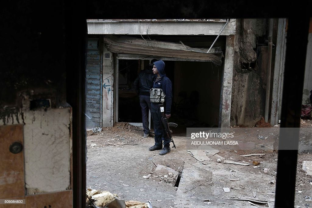 A rebel fighter, reportedly belonging to the Fajr al- Ummah brigade, holds his weapon as he stands on a street on February 10, 2016 in Harasta, east of the capital Damascus. / AFP / ABDULMONAM EASSA
