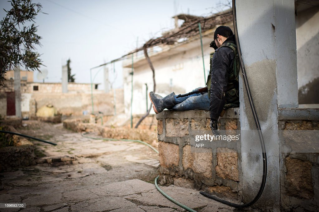A Rebel fighter rests in a rebel control area in the city of Aleppo on January 18, 2013. UN leader Ban Ki-moon warned that Syria is in a 'death spiral', as his top humanitarian and human rights officials pleaded with the UN Security Council to take firmer action. AFP PHOTO / EDOUARD ELIAS