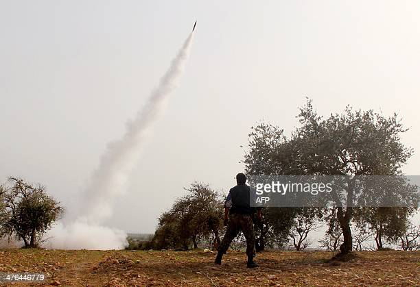 A rebel fighter stands back as a rocket is launched towards a progovernment forces position in the Syrian town of Khan Sheikhun in Idlib province on...