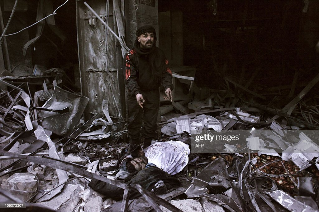 A rebel fighter stands next to the body of a man killed after a missile targeted a building in the al-Mashhad neighbourhood of Aleppo on January 7, 2013. The United Nations recently denounced a 'proliferation of serious crimes including war crimes' in Syria, as ever more horrifying images and videos emerge from the country. AFP PHOTO / ACHILLEAS ZAVALLIS