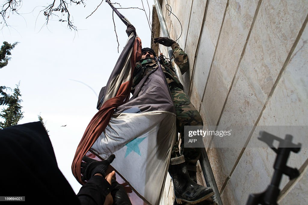 A Rebel fighter takes down a Syrian flag from a pole in the city of Aleppo on January 18, 2013. UN leader Ban Ki-moon warned that Syria is in a 'death spiral', as his top humanitarian and human rights officials pleaded with the UN Security Council to take firmer action. AFP PHOTO / EDOUARD ELIAS