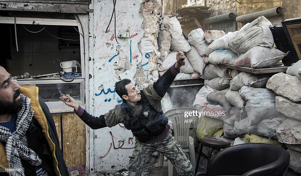 A rebel fighter throws a grenade towards a Syrian government forces position down an alleyway in the northern Syrian city of Aleppo on November 6, 2012. UN-Arab League peace envoy Lahkdar Brahimi said that the real risk for Syria is not partition but 'Somalia-isation', with the collapse of the state and the emergence of militia and armed factions. AFP PHOTO/JOHN CANTLIE