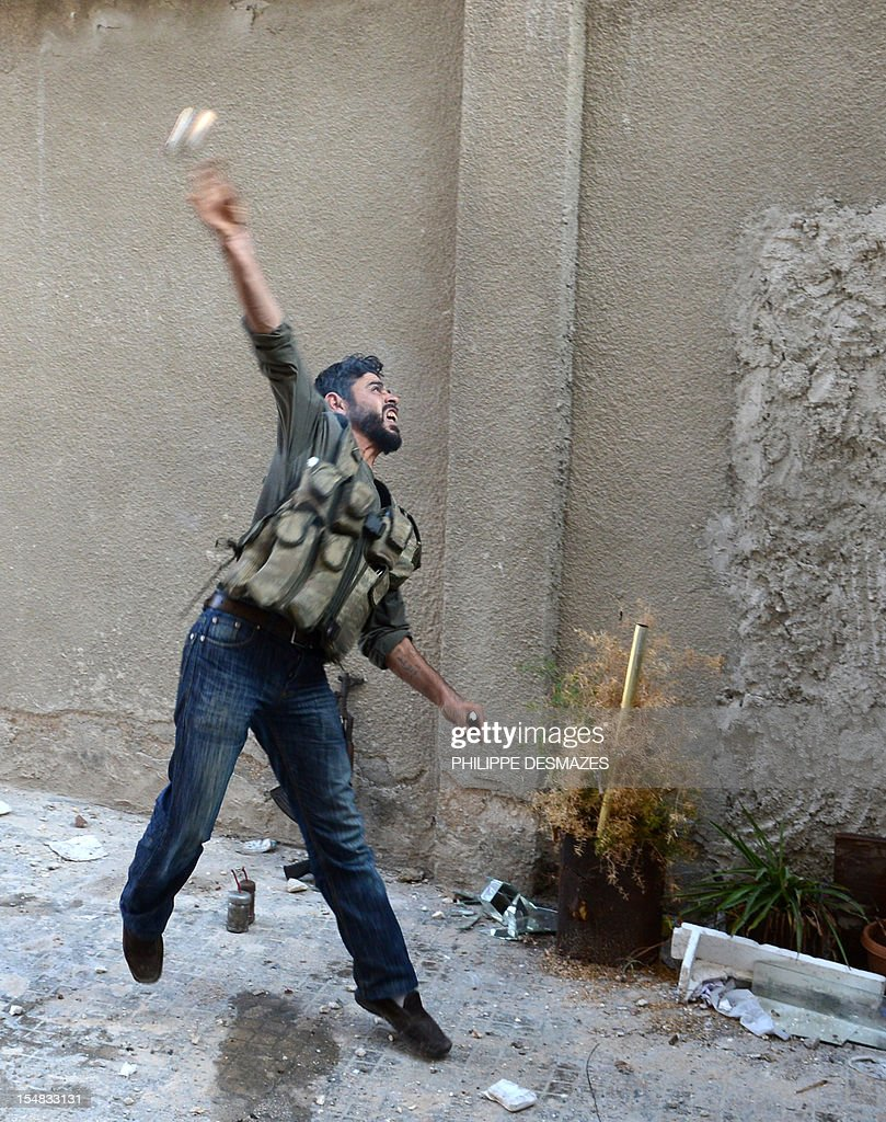 A rebel fighter throws a handmade hand grenade towards pro-Syrian government troops during fighting in the Bustan al-Bashar district of the northern Syrian city of Aleppo, on October 27, 2012. Syrian rebels clashed with Kurdish militia in the northern city of Aleppo, leaving 30 dead and around 200 captured, a watchdog said, sparking fears of a new front in an already fractured country.