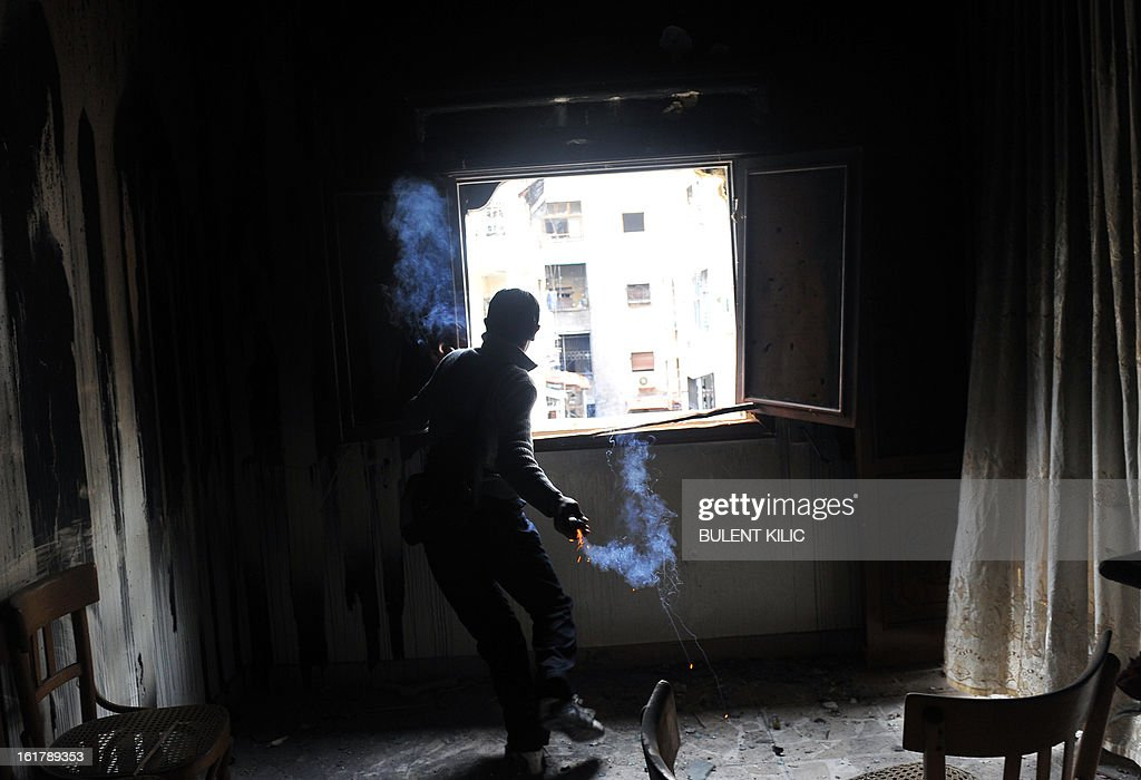 A rebel fighter throws a homemade grenade towards Syrian government forces through a window at a flat in the Salaheddine neighbourhood of Aleppo on February 16, 2013. More than 300 people were abducted by armed groups in northwestern Syria over two days in an unprecedented string of sectarian kidnappings, a watchdog and residents said.