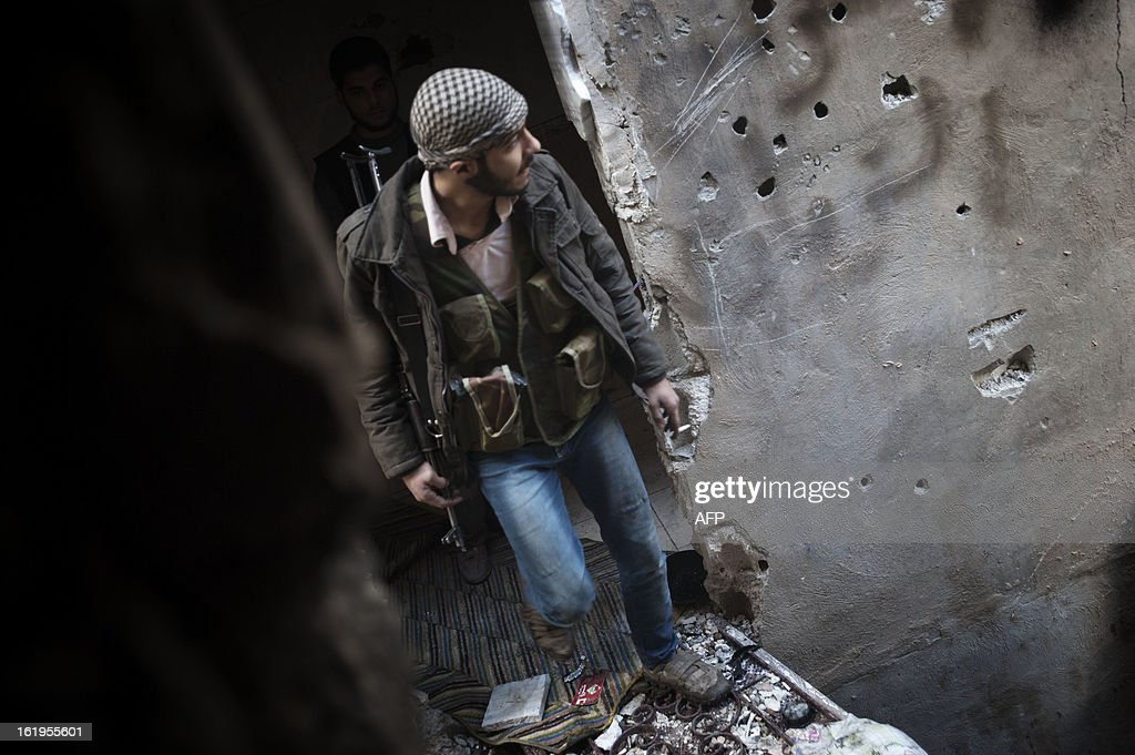 A rebel fighter walks along a makeshift bridge, attatching one of their bases to another, in the eastern city of Deir Ezzor, on February 16, 2013. Nine months of fierce fighting between rebel forces and regime troops, the largest city in eastern Syria is in ruins and more than two thirds of its inhabitants have fled.