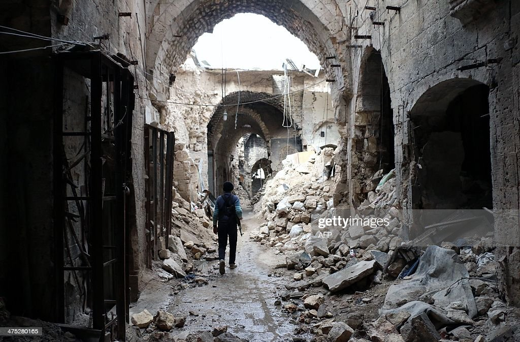 A rebel fighter walks in a devastated alley of Aleppo's old market in the UNESCOlisted northern Syrian city on February 27 2014 Some 3300 people have...