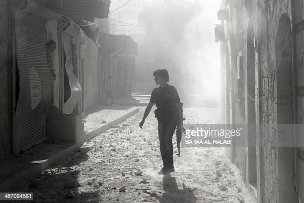 A rebel fighter walks on a street covered with dust in the Bab alQinnasrin area in Aleppo's Old city following a reported bombardment with...