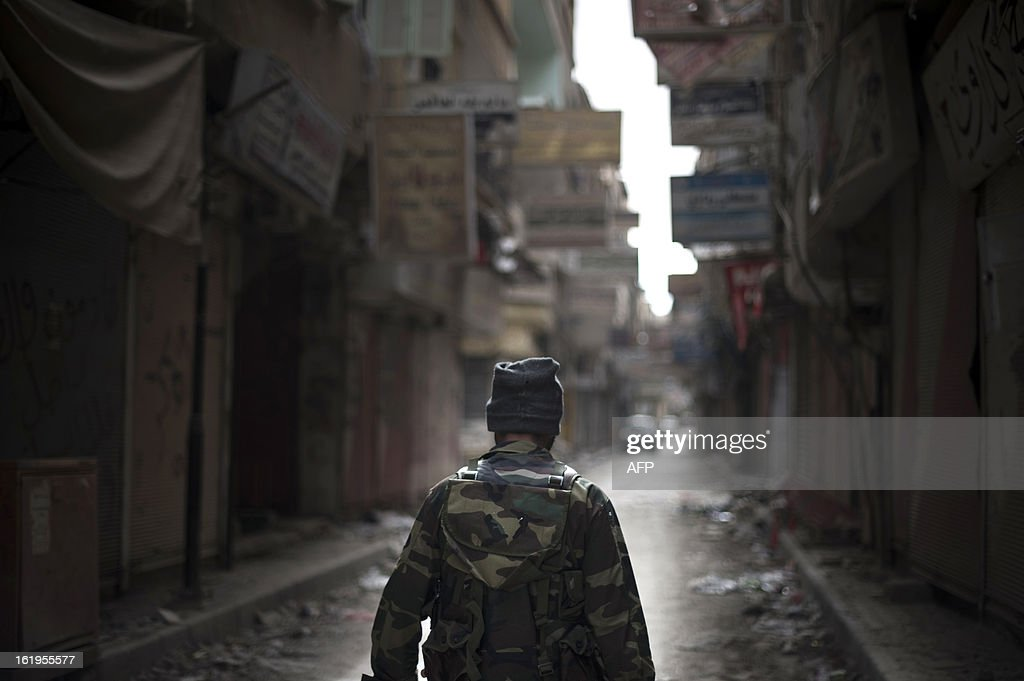 A rebel fighter walks through the Sit al-Ruba shopping street, ravaged and unused due to weeks of shelling, in the eastern city of Deir Ezzor, on February 16, 2013