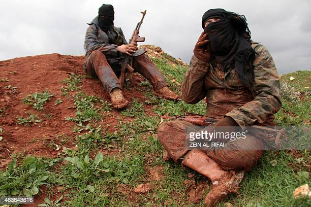 Rebel fighters are covered with mud as they hold a position on the frontline in the village of Ratyan in the countryside north of the Syrian city of...