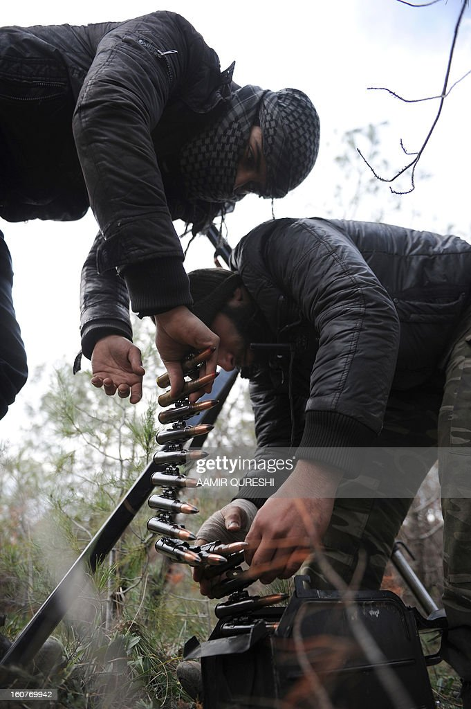 Rebel fighters check the ammunition for their heavy caliber weapon near their position as they prepare to fight against pro-Syrian regime forces on the Jabal al-Turkman mountains in Syria's northern Latakia province, on February 5, 2013.