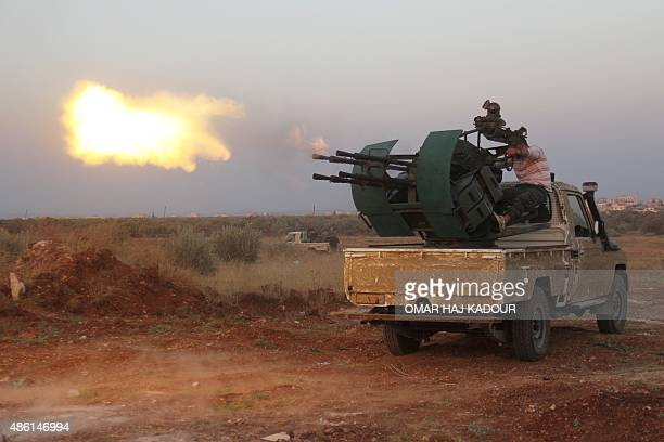 Rebel fighters fire a heavy machine gun during clashes with Syrian progovernment forces on the frontline facing Deir alZoghb a governmentheld area in...