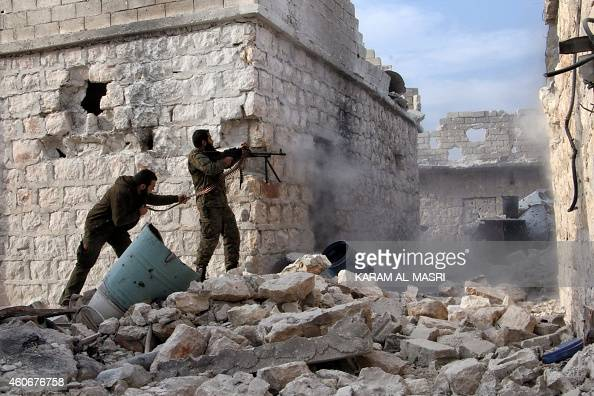 Rebel fighters fire a machine gun on the frontline during the battle against progovernment forces for control of the Handarat region located just...
