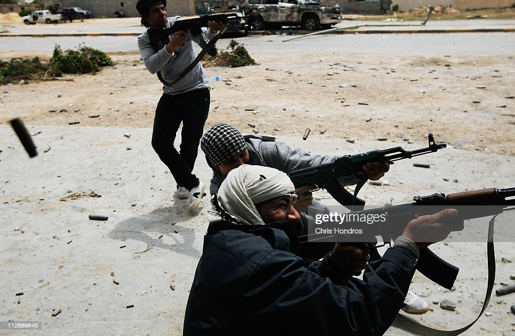 Rebel fighters fire at government loyalist troops during street fighting on Tripoli Street in downtown Misurata April 20, 2011 in Misurata, Libya. Rebel forces assaulted the downtown positions of troops loyal to Libyan strongman Moammar Gaddafi April 20, briefly forcing them back over a key bridge and trapping several in a building that rebel troops then surrounded. Fighting continues between Libyan government forces that have surrounded the city and anti-government rebels ensconced there.