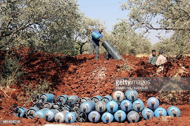 Rebel fighters fire homemade mortar rounds towards Syrian regime forces on July 20 on the outskirts of the Syrian city of Idlib AFP PHOTO / OMAR HAJ...