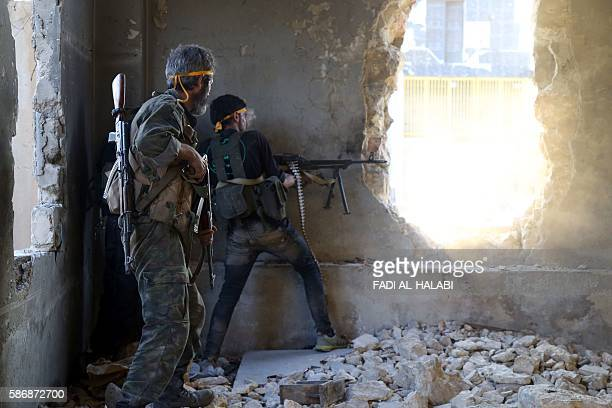 TOPSHOT Rebel fighters fire towards positions of regime forces in Ramussa on the southwestern edges of Syria's northern city of Aleppo on August 6...