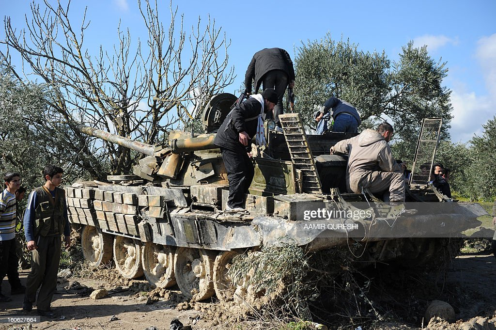 Rebel fighters fix a Soviet-made T-55 tank abandoned by the pro-Syrian regime forces in the Christian village of al-Yaqubia in northern Syria, near the border with Turkey, on February 2, 2013.