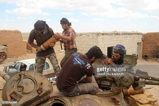 Rebel fighters from the Jaish alFatah brigades load ammunitions into a tank during clashes with Syrian progovernment forces near the village of Om...