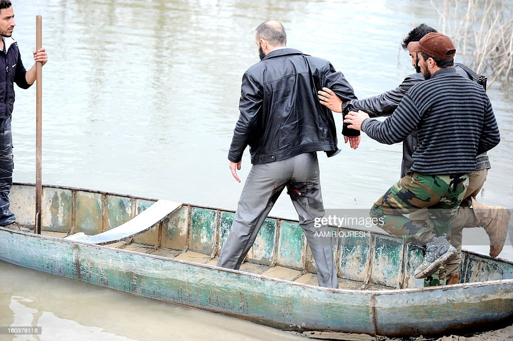Rebel fighters help their leader, who was injured during shelling by pro-Syrian regime forces, as he board a small boat that will take them across the Orontes river to Turkey near the northern Syrian town of Darkush on January 30, 2013. Syria's opposition chief Moaz al-Khatib said he is ready for dialogue with officials of President Bashar al-Assad's regime, subject to conditions including that some 160,000 detainees are released. The United Nations says more than 60,000 people have been killed in Syria's 22-month conflict.