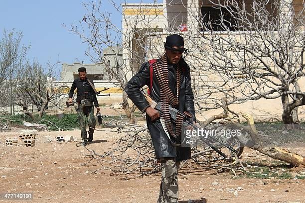 Rebel fighters make their way through a yard in the village of Morek in the countryside of the Syrian city of Hama on March 7 2014 More than 140000...