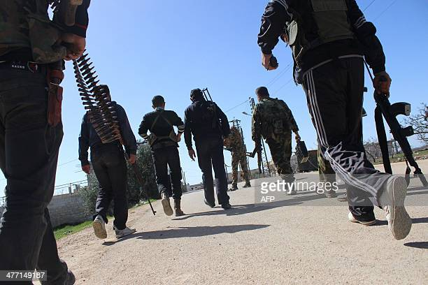 Rebel fighters make their way to the frontline in the village of Morek in the countryside of the Syrian city of Hama on March 7 2014 More than 140000...