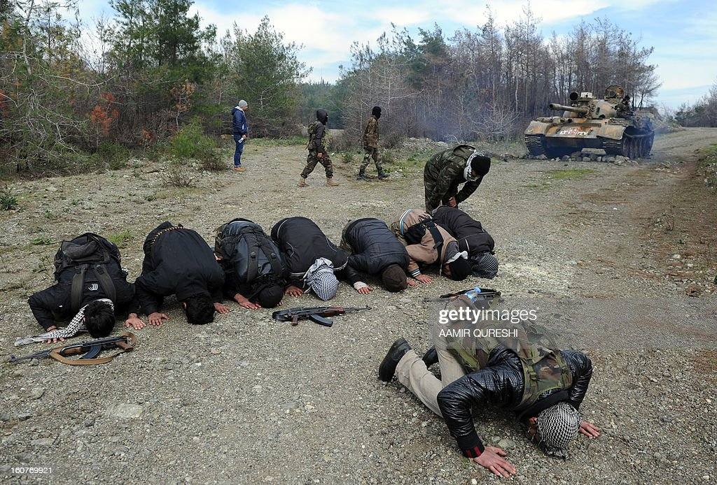 Rebel fighters offer prayers near their position as they prepare to fight against pro-Syrian regime forces on the Jabal al-Turkman mountains in Syria's northern Latakia province, on February 5, 2013.