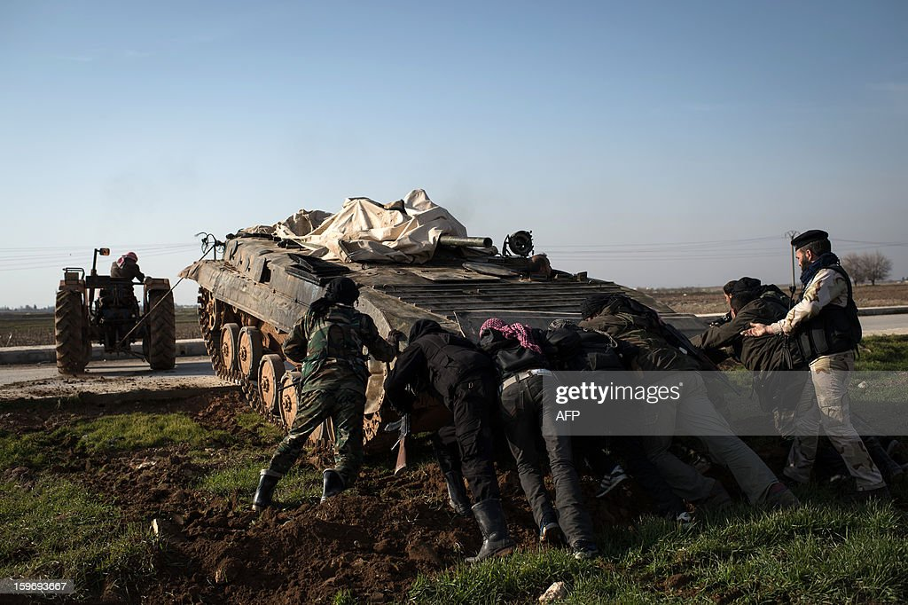 Rebel fighters push an abandoned Syrian army tank with the aid of a tractor, to be repaired and used by rebels, in the city of Aleppo on January 18, 2013. UN leader Ban Ki-moon warned that Syria is in a 'death spiral', as his top humanitarian and human rights officials pleaded with the UN Security Council to take firmer action.