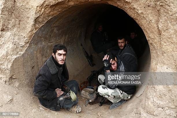 TOPSHOT Rebel fighters reportedly belonging to the Faylaq alRahman brigade wait in a concrete pipe during an operation in the area of Marj alSultan's...