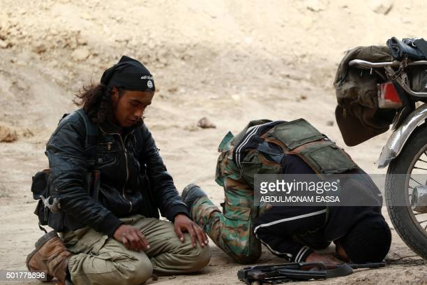 Rebel fighters reportedly belonging to the Faylaq alRahman brigade pray during an operation in the area of Marj alSultan's military airport three...
