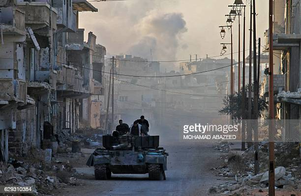 TOPSHOT Rebel fighters ride on a tank as smoke billows in the background during reported shelling by Syrian government forces in the rebelheld area...