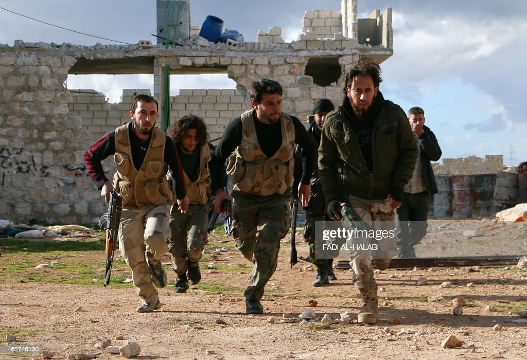 Rebel fighters run across the street as they hold a position in alMayasat a rebelcontrolled area of the northern Syrian city of Aleppo on February 4...