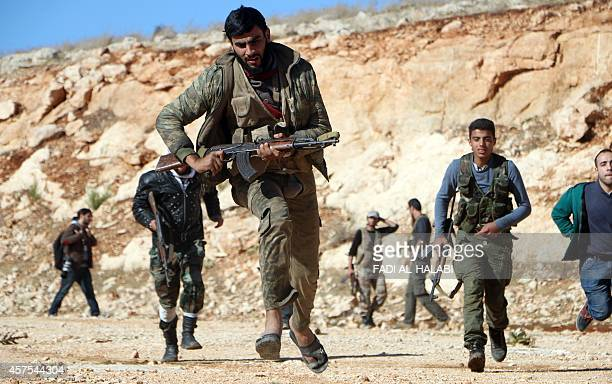 Rebel fighters run during a battle against Syrian government soldiers in Handarat on the northern outskirts of Aleppo on October 20 2014 Syrian...