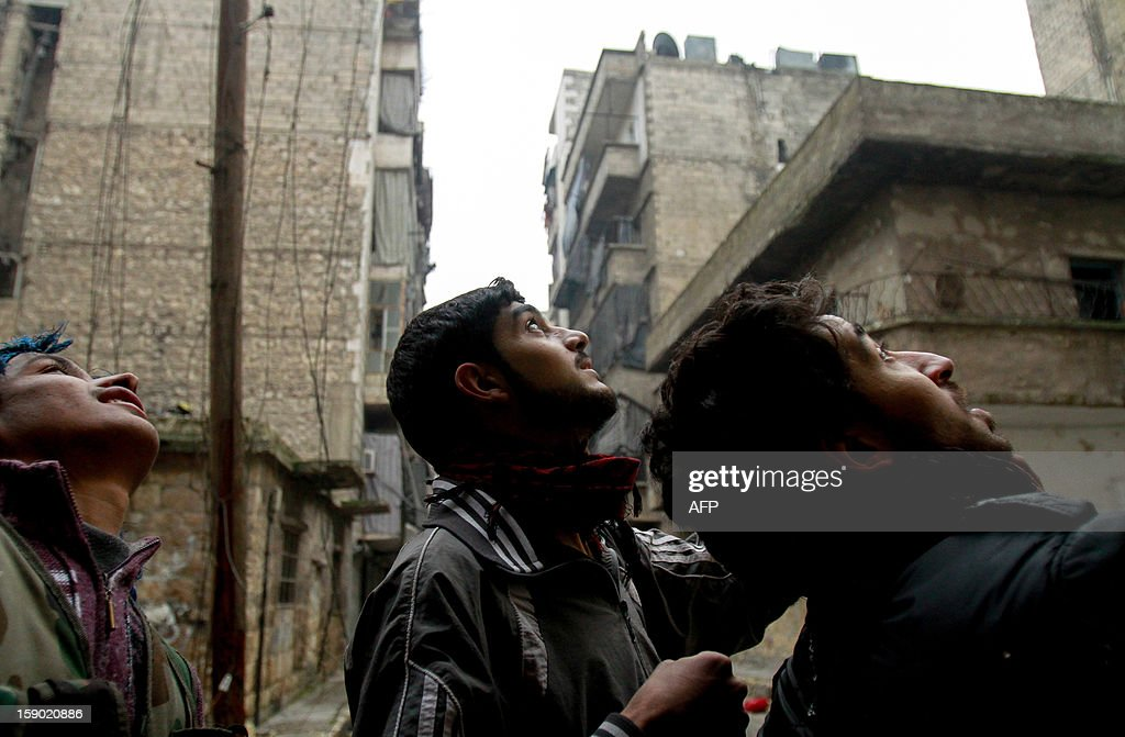 Rebel fighters search for pro-government snipers in buildings on the front line in the Salaheddine neighbourhood of Aleppo, where heavy fighting has been taking place on Januray 5, 2013. Saudi Arabia and Egypt called for a peaceful solution to the conflict roiling Syria, but said the terms of a settlement to end the bloodshed there must be defined by the Syrian people. AFP PHOTO/MAURICIO MORALES