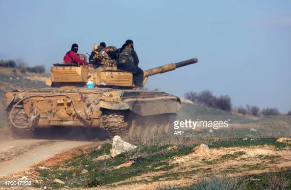 Rebel fighters sit on top of a tank as they head to the front line of battles against Syrian progovernment forces near the city of Hama on February...