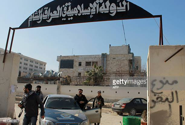 Rebel fighters stand at an entrance of the Aleppo headquarters of the Islamic State of Iraq and the Levant in the northern city of Aleppo after...