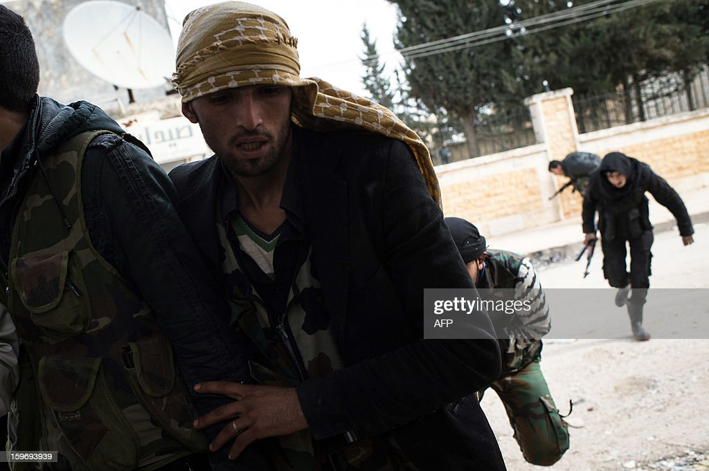 Rebel fighters take cover as they cross a street in the city of Aleppo on January 18, 2013. UN leader Ban Ki-moon warned that Syria is in a 'death spiral', as his top humanitarian and human rights officials pleaded with the UN Security Council to take firmer action.