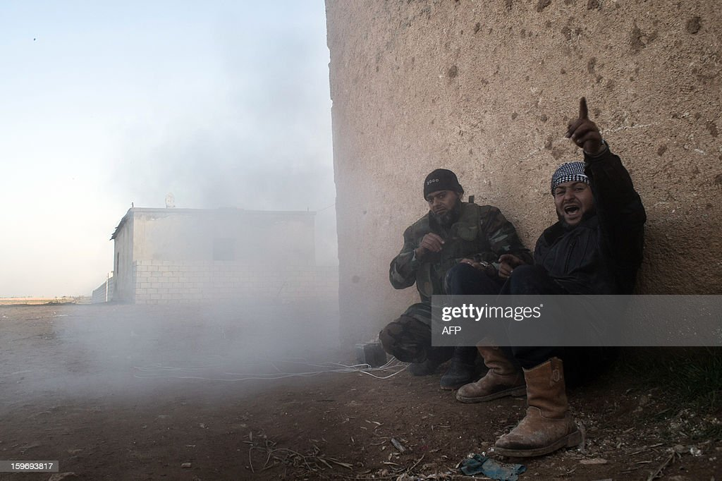 Rebel fighters take cover during a rocket launch in the city of Aleppo on January 17, 2013. UN leader Ban Ki-moon warned that Syria is in a 'death spiral', as his top humanitarian and human rights officials pleaded with the UN Security Council to take firmer action. AFP PHOTO / EDOUARD ELIAS