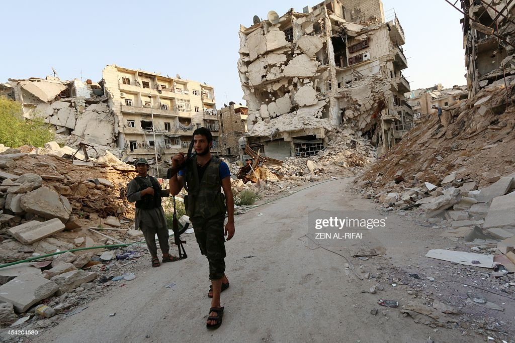 Rebel fighters walk in front of damaged buildings in Karm alJabal neighbourhood of Aleppo on August 26 2014 The United States has begun...