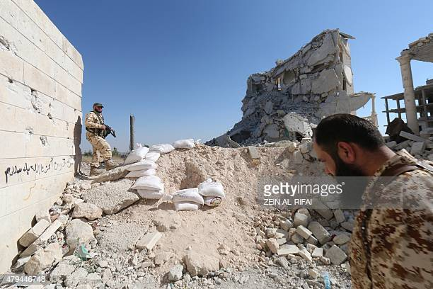 Rebel fighters walk on the rubble of destroyed buildings at a former research centre being used as a military barracks after they captured the...
