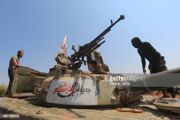 Rebel forces from Jaysh alIslam stand on a tank as they hold a position on August 24 2015 near the frontline in the alZahra area on the northwestern...