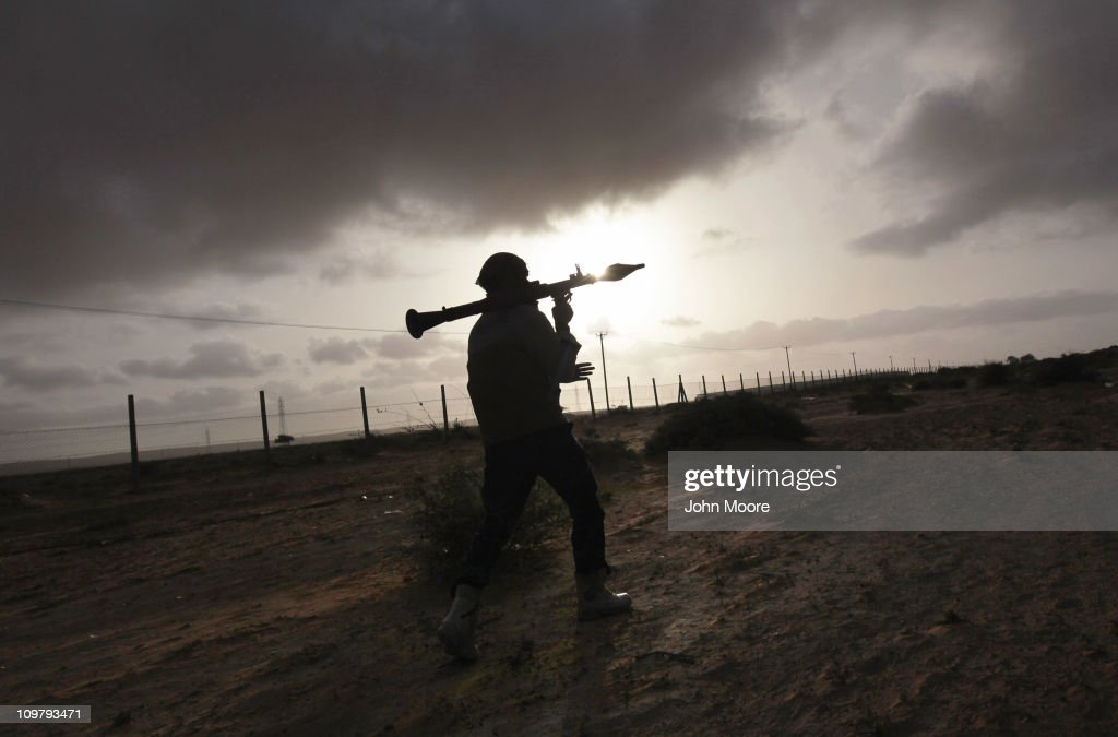 A rebel militiaman carries a rocket propelled grenade while advancing on the frontline March 25 2011 in Ben Jawat Libya Opposition forces pushed...