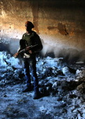 A rebel militiaman stands in the ashes of an alleged torture chamber of the former Libyan Internal Security force on February 28 2011 in Benghazi...