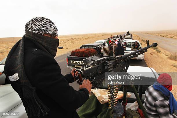Rebel militiamen ride atop pickups with mounted weapons known as 'technicals' while moving towards the frontline March 25 2011 in Ben Jawat Libya...