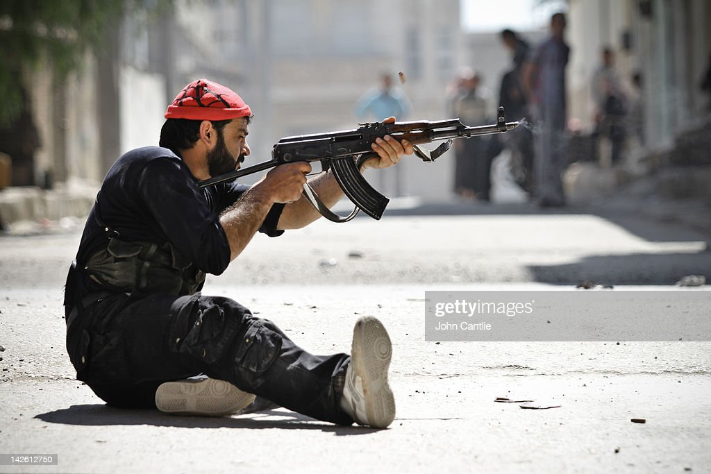 A rebel of the Free Syrian Army fires his Kalashnikov at government tanks that have advanced into Saraquib city on April 9, 2012 in Syria. Conitnuing violence in northern Syria between government forces and rebels is putting plans for a UN-brokered Syria ceasefire on Tuesday in jeopardy.