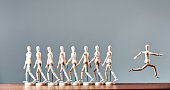 A single wooden lay figure turns away from a line of marchers and escapes, running in the opposite direction.
